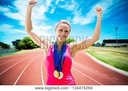 Portrait of happy sportswoman is winning against high angle view of track