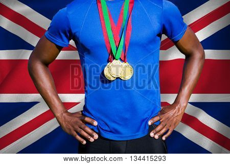 Portrait of athletic man chest holding gold medals against digitally generated uk national flag