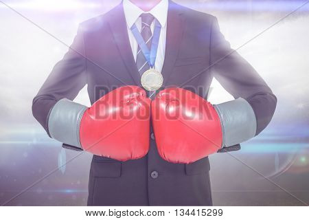 Businessman with boxing gloves against american football arena