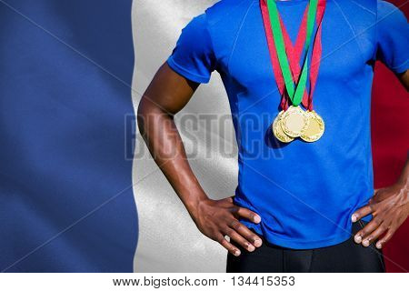 Portrait of athletic man chest holding gold medals against digitally generated france national flag
