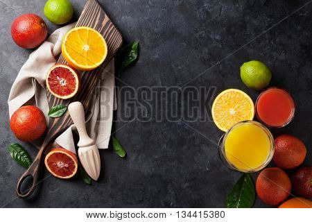 Fresh citruses and juice on dark stone background. Oranges and limes. Top view with copy space
