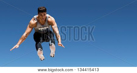Front view of sportsman is jumping against scenic view of blue sky