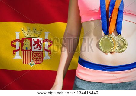 Close up of sportswoman chest with medals against digitally generated spanish national flag