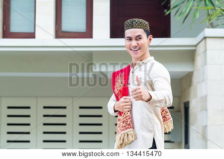 Asian Muslim choosing house wearing traditional dress
