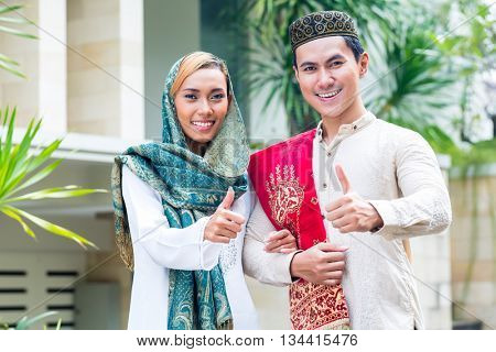 Asian Muslim man and woman choosing house wearing traditional dress