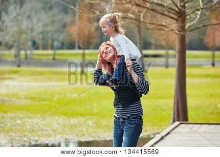 Mother holding daughter sit in her shoulders at the park lake