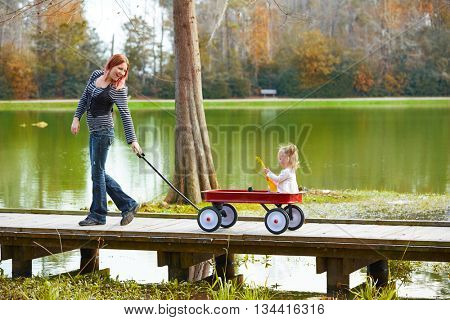 Kid girl and mother walking in the park lake with pull cart