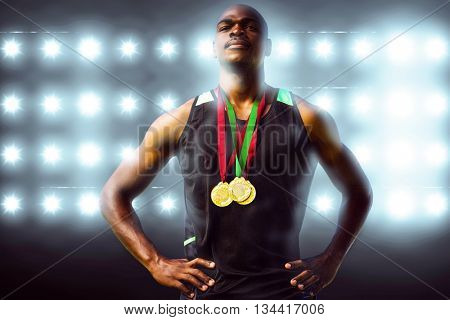 Athletic man posing with his medals against digitally generated image of blue spotlight