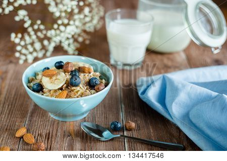Breakfast with oatmeal porridge with berries and nuts. milk porridge in blue bowl on brown wood table. horizontal, colorfull