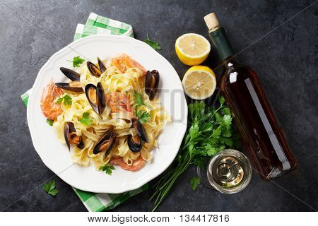 Pasta with seafood and white wine on stone table. Mussels and prawns. Top view