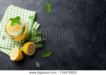 Lemonade pitcher with lemon, mint and ice on stone table. Top view with copy space