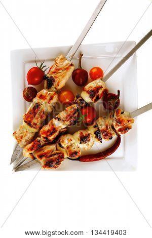 chicken shish kebab on white platter with vegetables