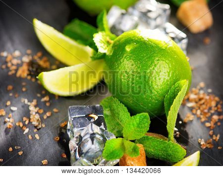 Background of Mojito cocktail ingredients on a table in summer bar, Alcohol cocktails with Rum, lime, mint, ice cubes and brown sugar closeup, Party drink. Isolated on black background