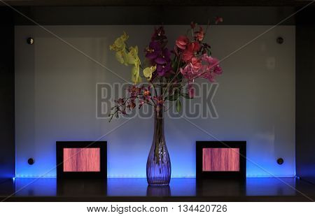 Shelf with lighting decoration flowers in bowl and frames against multicolor backlit plastic panel