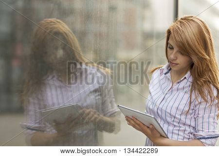 Young business woman working on her tablet computer outside of the office