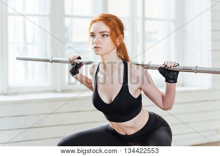 Close-up portrait of a young fitness healthy woman doing exercises with barbell at the gym