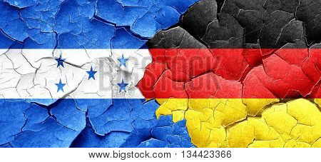 Honduras flag with Germany flag on a grunge cracked wall