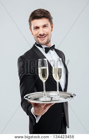 Smiling young waiter in tuxedo offers you glass of champagne over white background