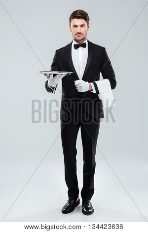 Full length of confident young waiter in tuxedo standing and holding tray over white background