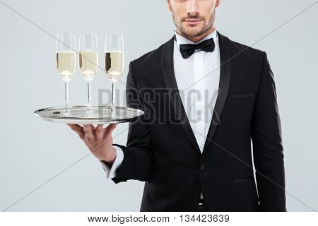 Closeup of waiter in tuxedo and bow tie holding tray with glasses of champagne over white background
