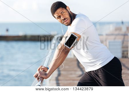 Serious african american sportsman listening to music fron blank screen smartphone on pier