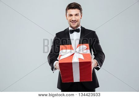 Cheerful attractive young man in tuxedo giving you red gift box over white background