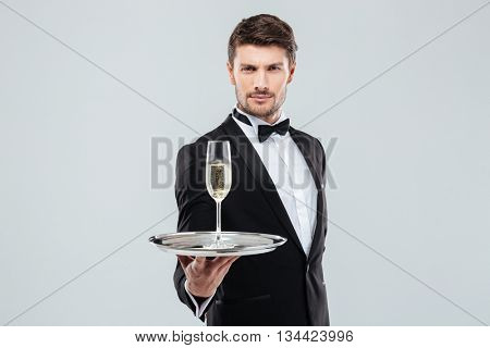 Attractive young butler in tuxedo with bow tie offers you glass of champagne over white background