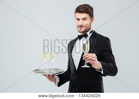 Attractive young waiter in tuxedo holding tray and glass of champagne over white background