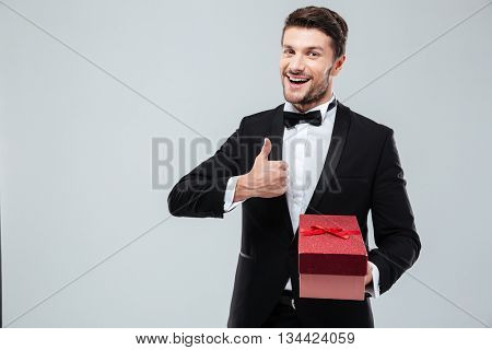 Smiling handsome young man in tuxedo holding present box and showing thumbs up over white background