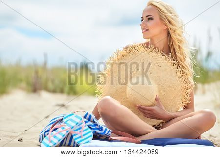 Photo of sexy woman on the beach, attractive female with  big fashionable sun hat