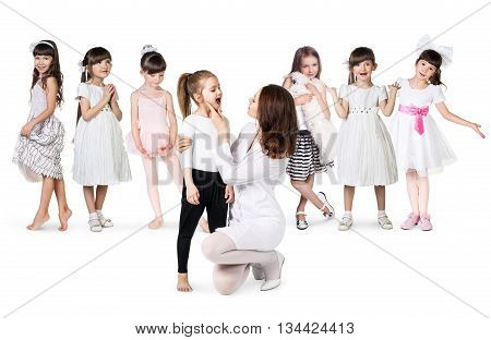 Doctor examining throat of little girl on the many girls backgound isolated on white