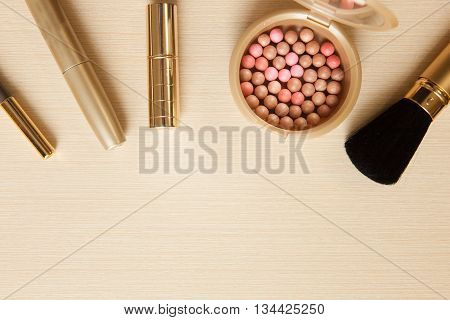 Golden Cosmetics - Mascara, Lipstick, Powder, Blusher, Brush Pencil On Light Wooden Background With