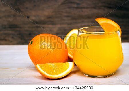 Navel orange juice and slices of orange on wooden background