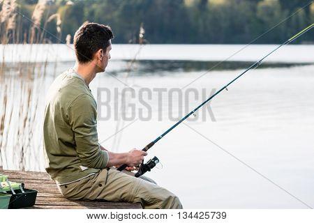 Man relaxing fishing or angling at lake sitting cross-legged on jetty