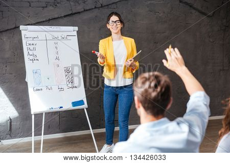 Cheerful young business woman making presentation and answering questions of audience in office