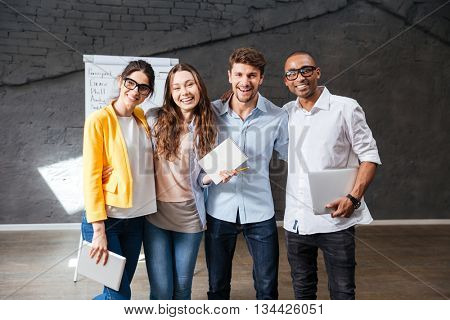 Multiethnic group of happy young business people holding tablet and laptop standing in office