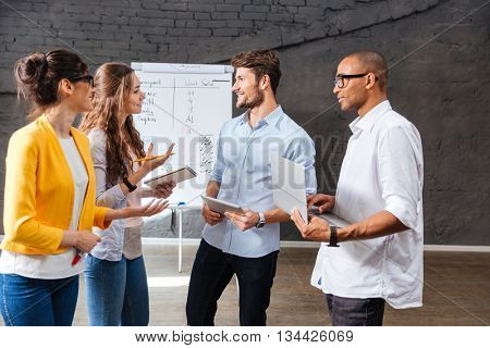 Multiethnic group of smiling young business people standing and talking in conference room