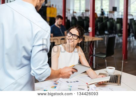 Cheerful young business woman in glassses talking to her collegue with tablet in office