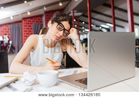 Tired sleepy young business woman in glasses sitting and working with laptop in office