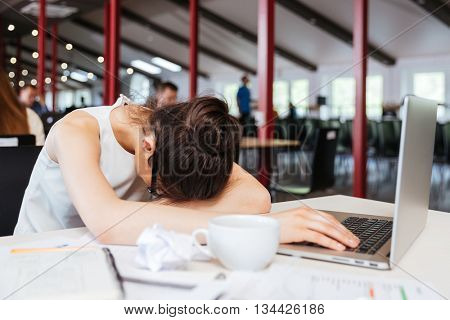 Exhausted fatigued young business woman sleeping on table with laptop at workplace