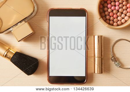 Smartphone With Empty Screen And Golden Cosmetics - Lipstick, Powder, Blusher, Brush, Perfume, Brace