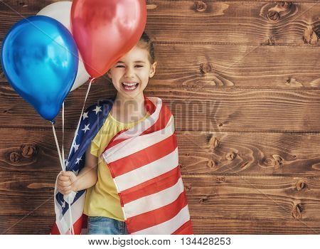 Patriotic holiday. Happy kid, cute little child girl with American flag. USA celebrate 4th of July.