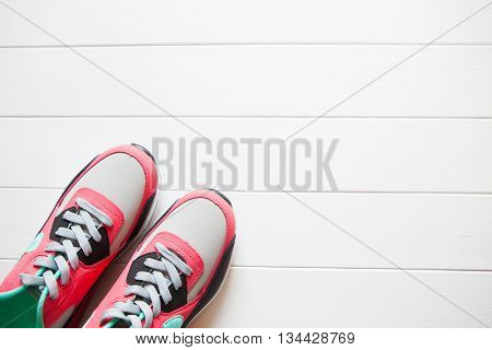 red and grey sneakers with grey shoelaces on white wooden background indoors