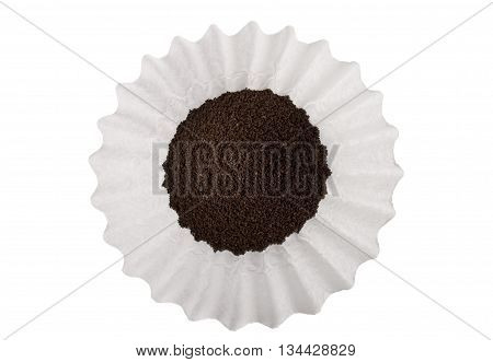 Ground coffee scooped into a white basket style coffee filter isolated on white.