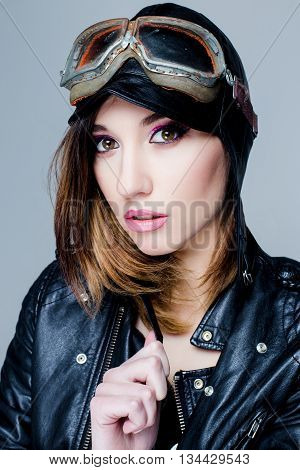 Portrait of Sexy biker woman with US Army-style motorcycle helmet with goggles