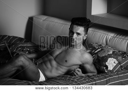 Handsome young man with athletic muscular body and bare torso laying in bed in morning black and white