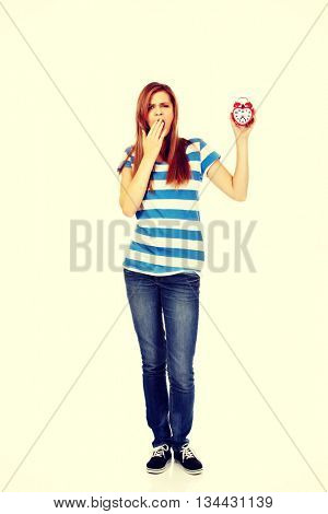 Yawning teenage woman holding alarm clock