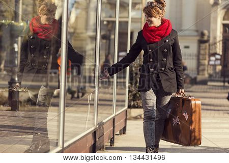Beautiful young girl walking by a shop window carrying a suitcase