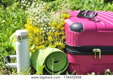 Pink suitcase with thermos wildflowers and yoga mat