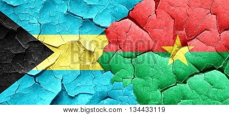 Bahamas flag with Burkina Faso flag on a grunge cracked wall